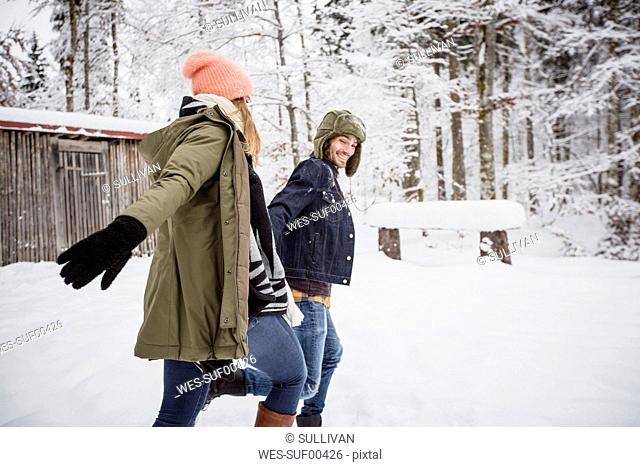 Happy couple running outdoors in winter
