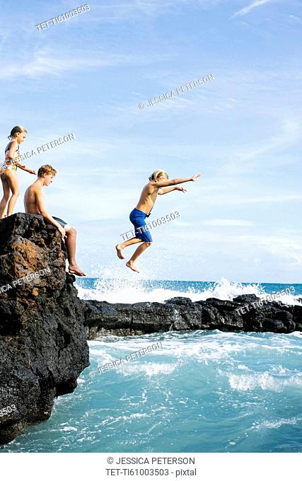 Man and girl (6-7) resting on cliff and boy (8-9) jumping