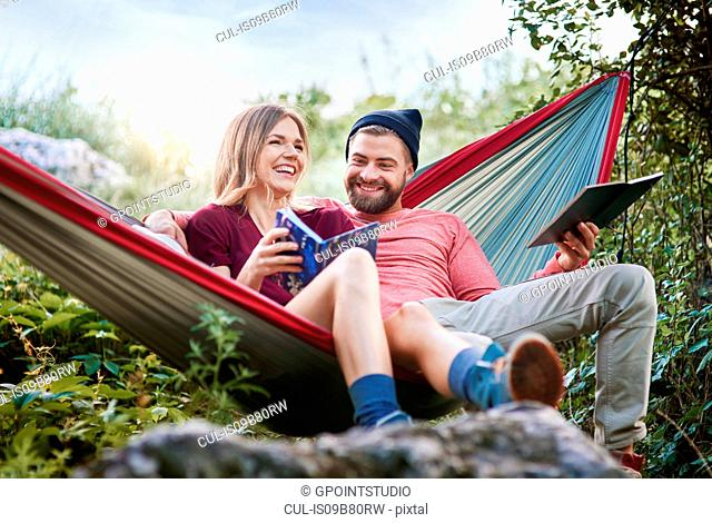 Couple relaxing in hammock, smiling, Krakow, Malopolskie, Poland, Europe
