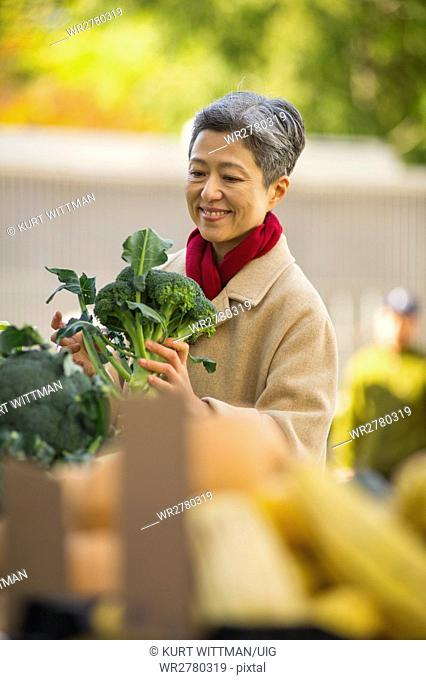 Woman Shopping for Vegetables At Public Market