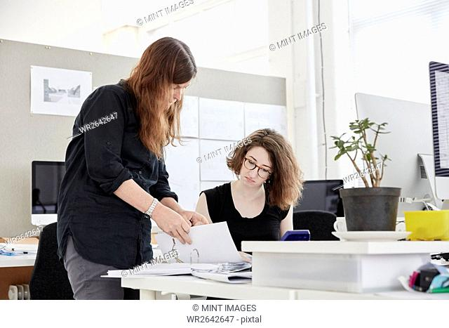 A modern office. Two women, one standing and one seated, discussing paperwork