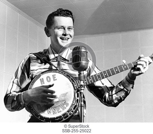 Front view of a young man singing and playing the banjo