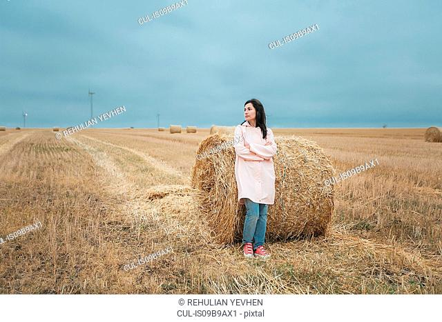 Woman in raincoat by hay bale, Odessa, Ukraine