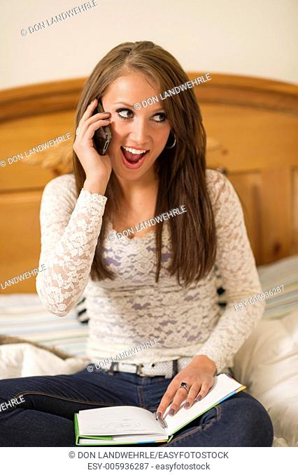 Teenage girl lying on a bed talking on a cell phone while doing homework