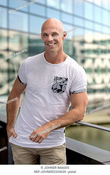 Smiling man standing on balcony