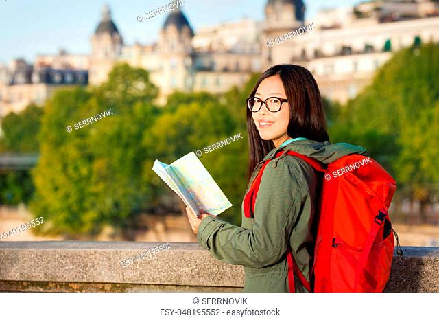 Young Asian girl walking along embankment of the Seine River with big red backpack and map of Paris