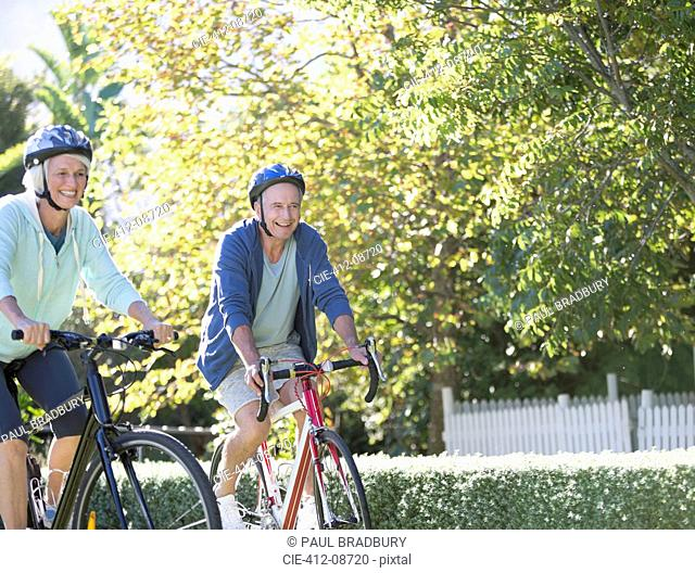 Senior couple riding bicycles in park