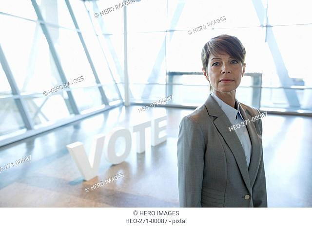 Portrait confident businesswoman near Vote text