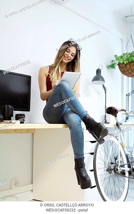 Smiling casual young woman sitting on desk in the office taking notes