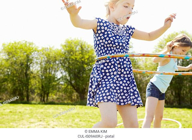 Low angle view of two girls playing with plastic hoops