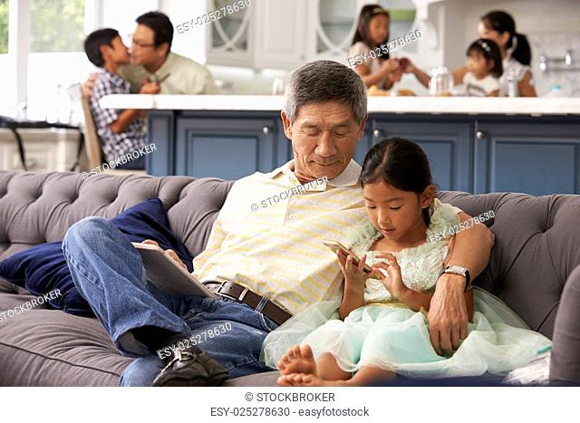 Grandfather And Granddaughter Using Mobile Phone At Home