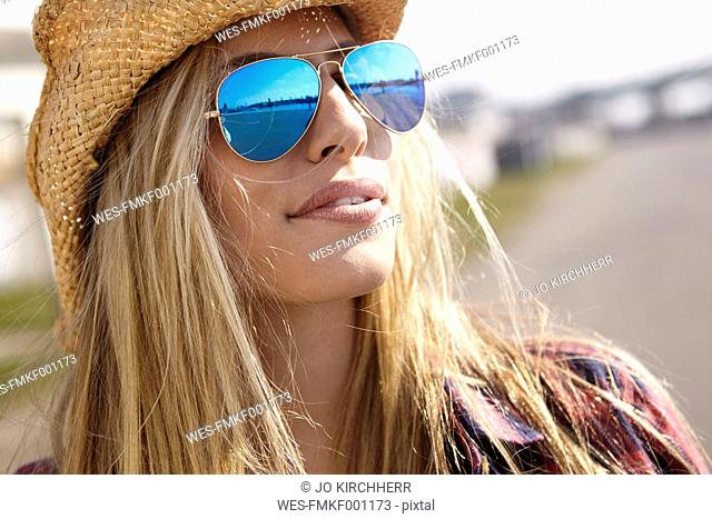 Young woman wearing cowboy hat and sunglasses