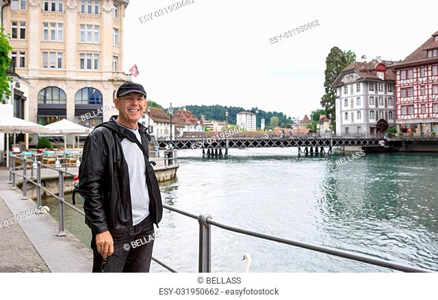 Happy Tourist in Lucerne, Switzerland with Reuss River and shops behind
