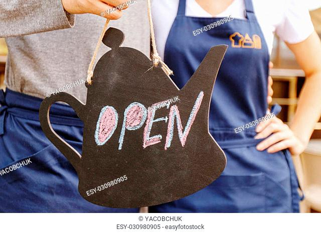 Always open. Two cafeteria workers holding sign open