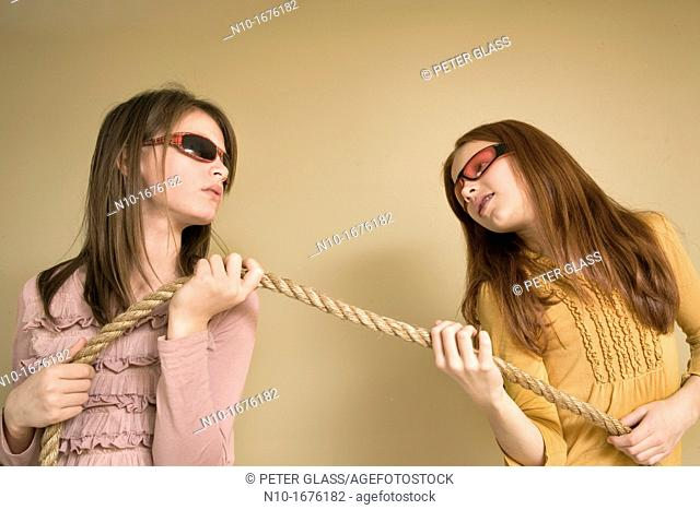 Preteen girls, wearing sunglasses, pulling on a rope