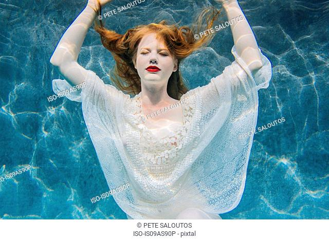 Young woman underwater, wearing thin white shirt