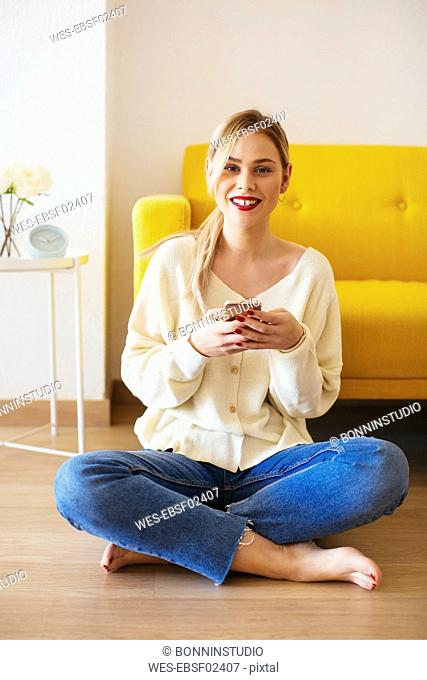 Blonde woman using smartphone at home