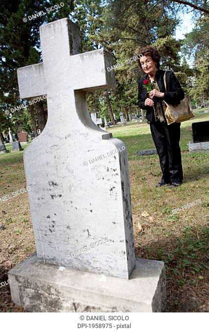 A Woman Visits A Grave In A Cemetery; Edmonton, Alberta, Canada