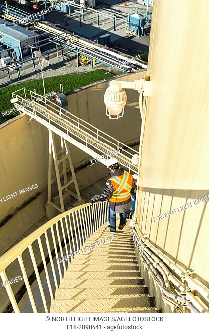 Canada, BC, Delta. Worker descends exterior staircase on the outside of LNG (liquefied natural gas) storage tank. Port of Delta on the Fraser River