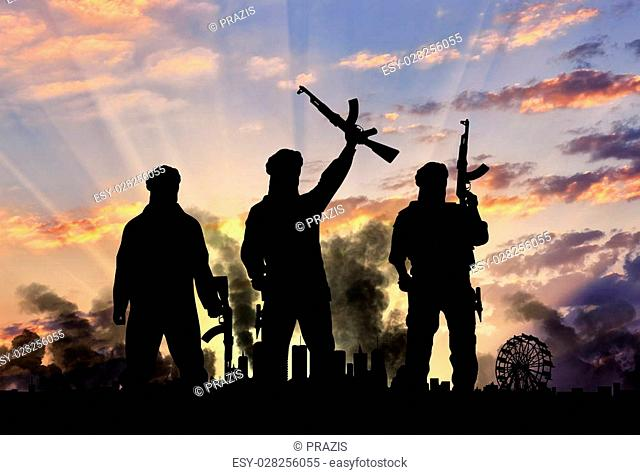 Concept of terrorism. Silhouette of the terrorists and the city in smoke against the sunset