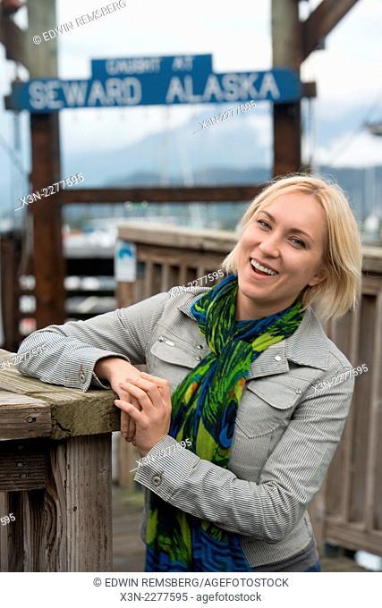 Blonde woman in front of marina in Seward Alaska