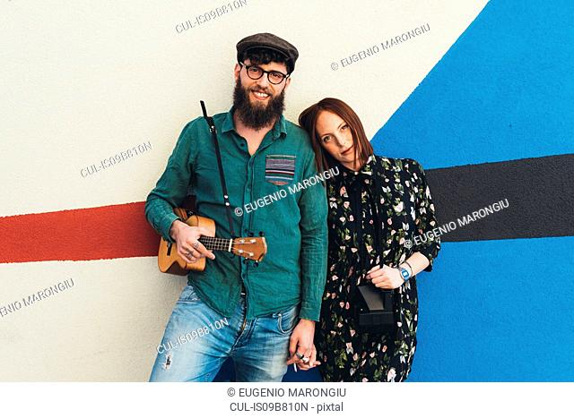 Portrait of cool couple leaning against abstract wall