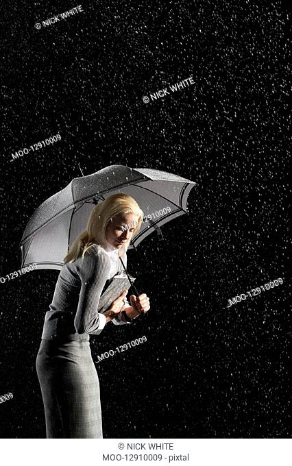 Businesswoman hunching down Under Umbrella for protection from rain