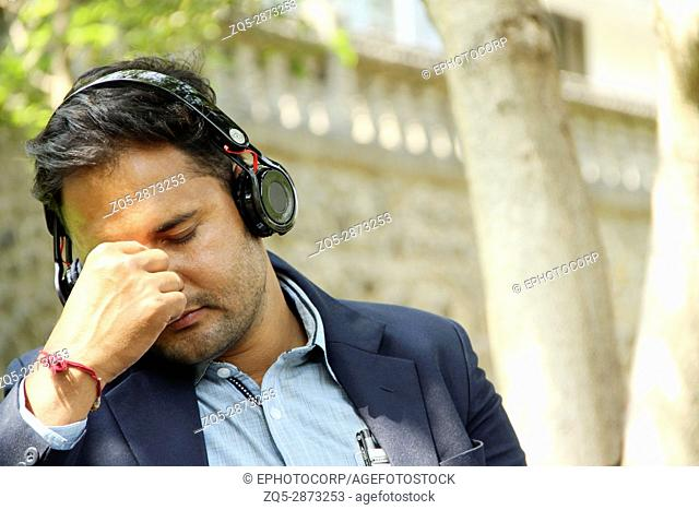 Young Indian corporate man listening to music closing his eyes in park