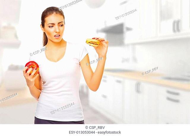 Girl with hamburger and apple ay kitchen