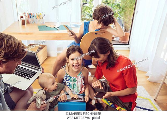 Happy playful family using digital devices in children's room