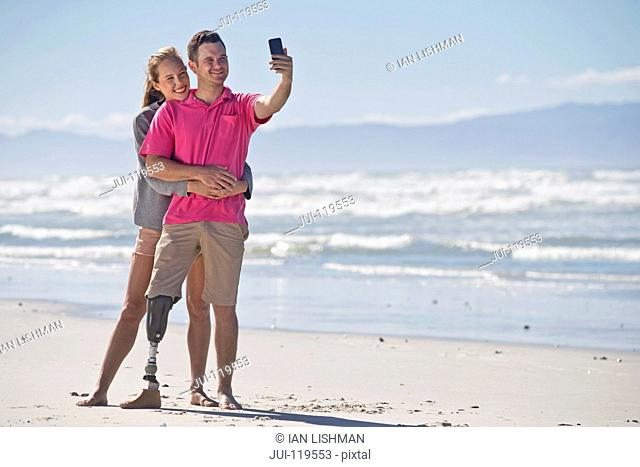 Man With Artificial Leg Posing For Selfie With Female Partner Whilst On Summer Beach Vacation In South Africa