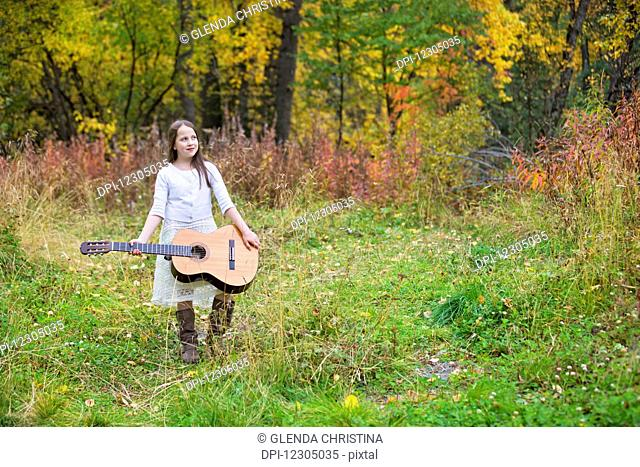 Young girl holding a guitar outdoors in the Hatcher Pass area, Southcentral Alaska, autumn