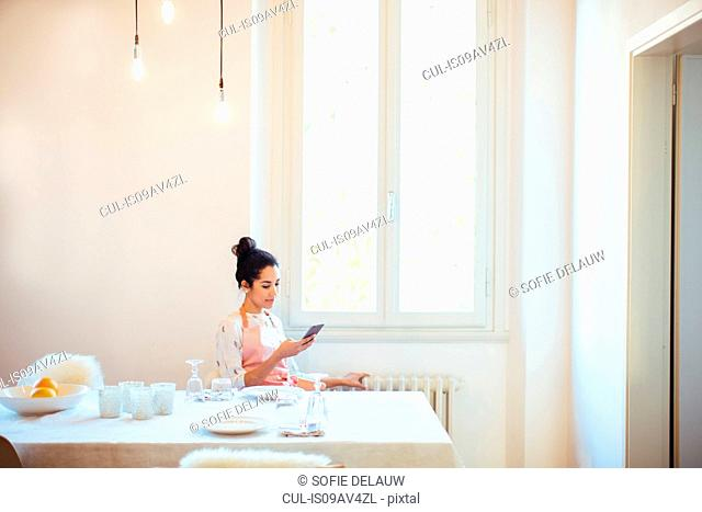 Young housewife wearing apron at table reading smartphone text