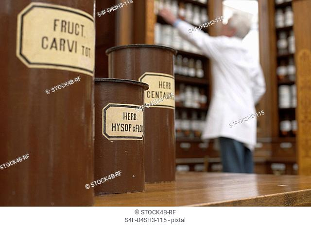 Containers for several medicinal herbs, pharmacist in background