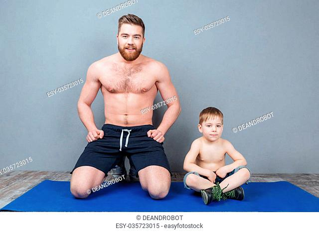 Happy dad and song sitting on blue yoga mat together
