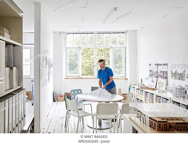 A modern office. A man looking at plans at a table, architectural drawings. Building models on shelves. Open windows. Summer