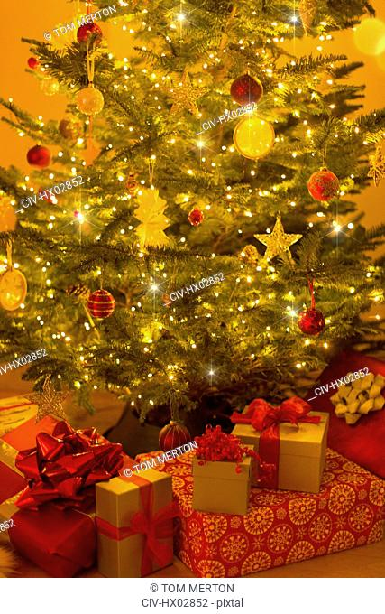 Illuminated Christmas tree with ornaments and gifts