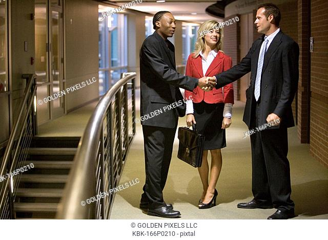 Side view of businesspeople standing in an office hallway and lobby shaking hands