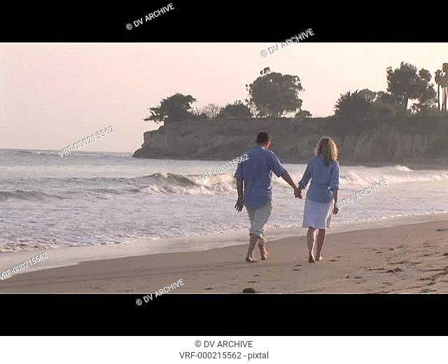 Medium shot of a couple strolling on the beach