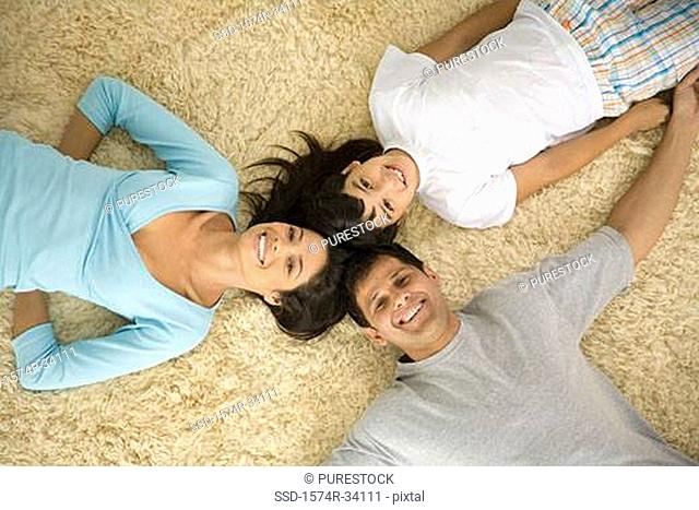 High angle view of a mature man and a young woman lying on a rug with their son