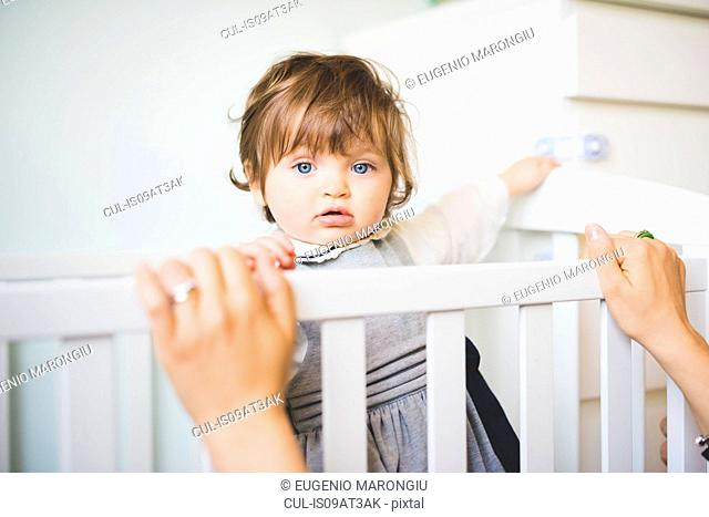 Portrait of female toddler staring from crib