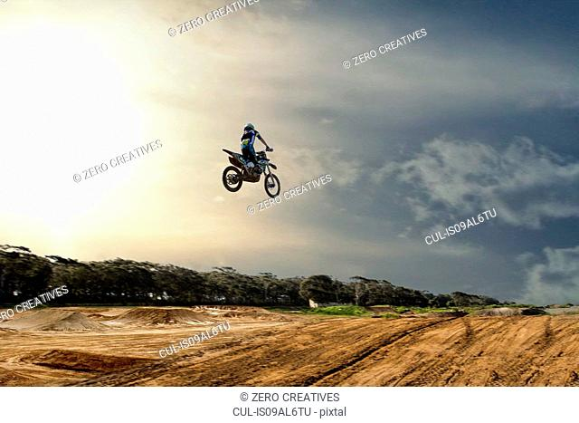 Silhouetted young male motocross racer jumping mid air over mud track