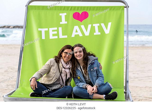 A mother and daughter sit together in a large chair on the beach which says I love Tel Aviv; Tel Aviv, Israel
