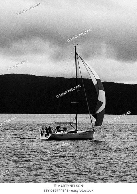 This sailboat under a cloudy sky on the Northern Oregon coast is rendered here in black and white