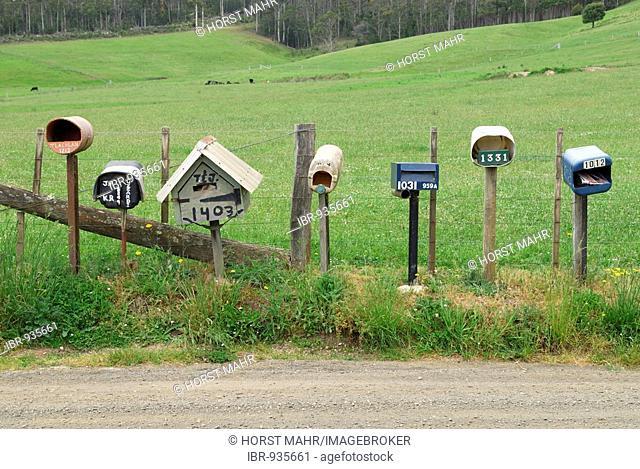 Post boxes of different farmhouses on the side of a road near Deloraine, Tasmania, Australia