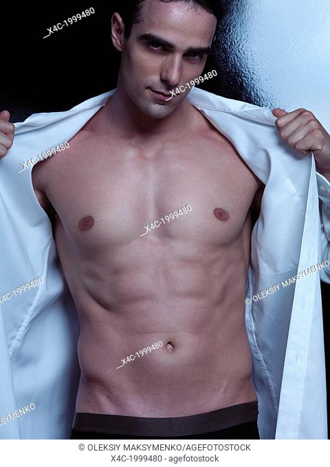 Expressive portrait of a sexy young handsome man with muscular bare torso taking off his shirt