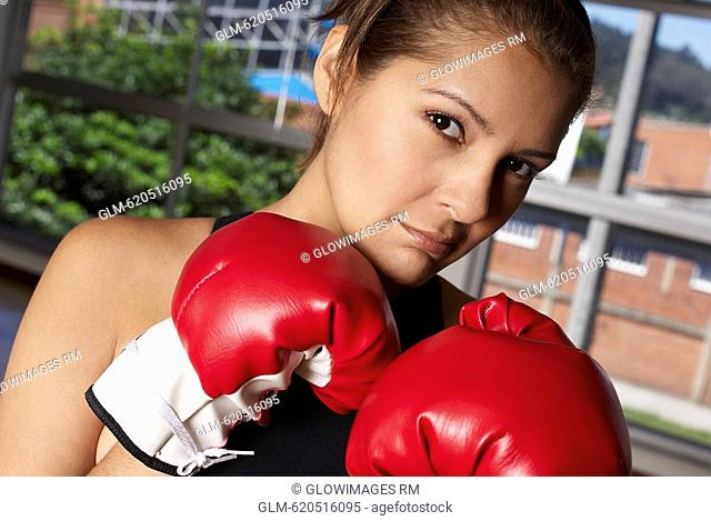 Portrait of a young woman wearing boxing gloves