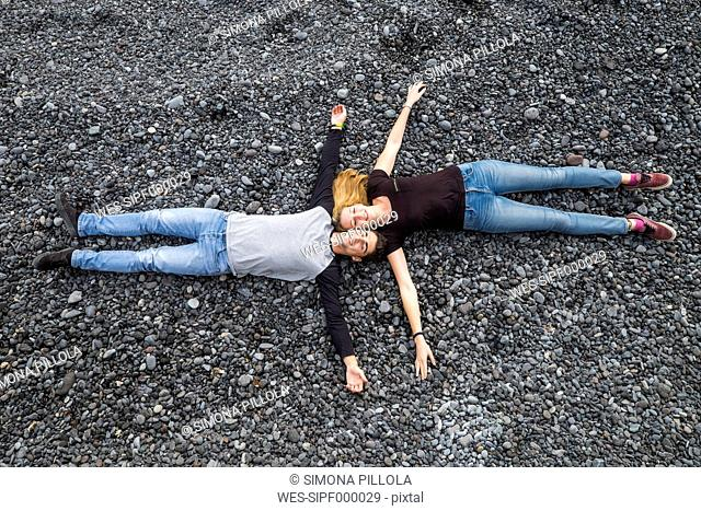 Relaxed young couple lying on stones