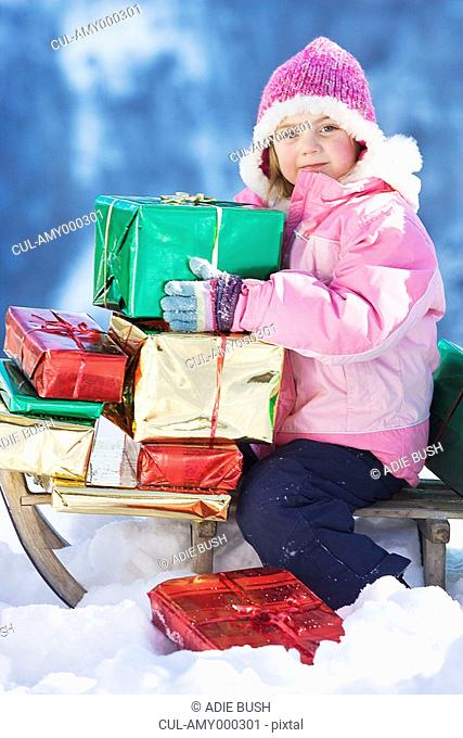 Portrait of girl on sledge with presents
