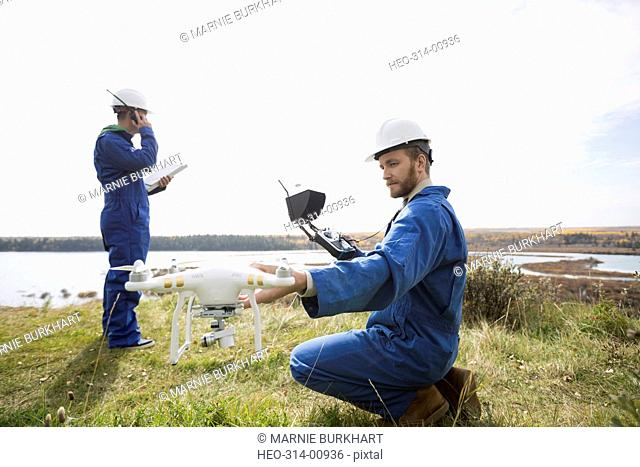 Surveyors with drone equipment on hill overlooking lake